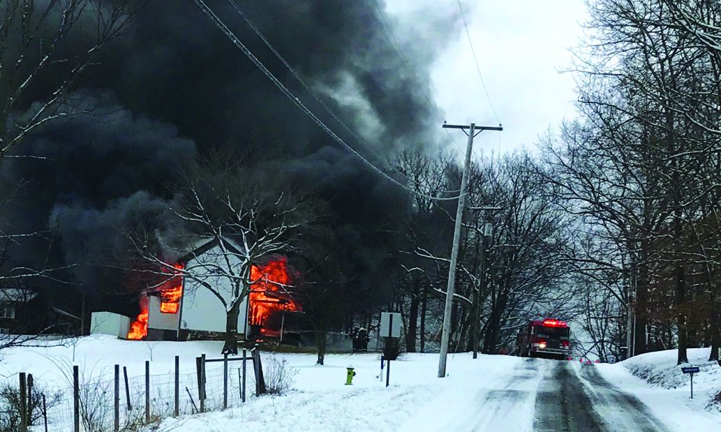 Special to the Journal/Gary Tolson Flames and smoke pour from a home on Crews Road in Madison Township.