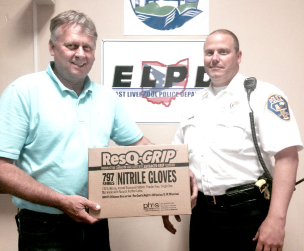 Morning Journal/Jo Ann Bobby-Gilbert Pepper Locke (left), sales manager for PH and S Products LLC in Minerva, presented a case of protective nitrile gloves to Chief John Lane of the East Liverpool Police Department Thursday. Locke's company learned through news accounts about ELPD Patrolman Chris Green's recent exposure to suspected opiate drugs during a traffic stop that caused him to overdose and said company officials wanted to donate some of the gloves they produce for officers' safety.