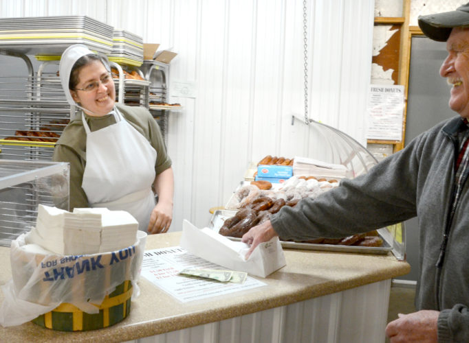 "Morning Journal/Patti Schaeffer Mary Byler, owner of Mary's Homemade Donuts and Coffee at the Rogers Community Auction and Open Air Market shares a light moment early on a Friday morning with D.R. ""Doc"" Roberts of Lisbon. Mary and her workers began making the large pastry treats at 5 a.m. and went strong until 7 p.m. that evening."