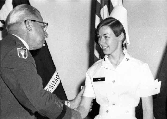 In this Aug. 30, 1968, photo provided by Philip Bigler, author of Hostile Fire, U.S. Army nurse Sharon Lane is congratulated by a military official as she's promoted to first lieutenant in Aurora, Colo. Lane, the only American servicewoman killed by hostile fire in the Vietnam War, has been immortalized in books, statues and a television show, and veterans still gather at her grave five decades after her death. (U.S. Army/Hostile Fire/Vandamere Press via AP)