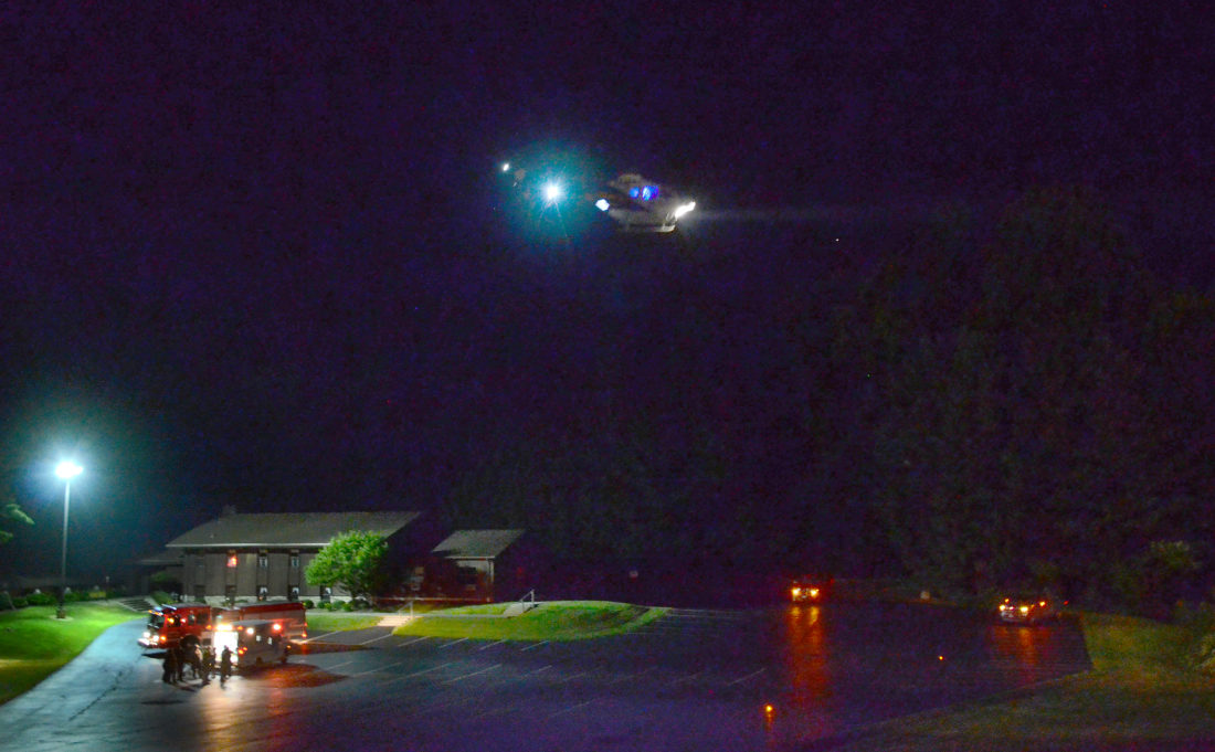 Morning Journal/Patti Schaeffer A STAT Med-Evac helicopter nears the Winona Friends Church where Winona firefighters and an ambulance wait. A man had been pinned underneath a truck at a Whinnery Road home.