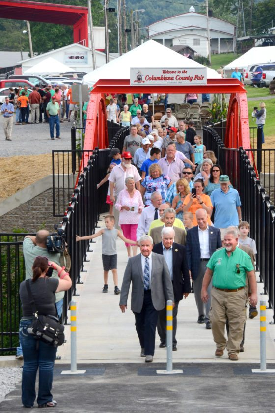 Morning Journal/Patti Schaeffer Following the dedication ceremonies, honorees and attendees were invited to follow county engineer Bert Dawson and fair board president John Wolf across the historic bowstring arch bridge walkway as they led a tour to the newly re-constructed administration offices.