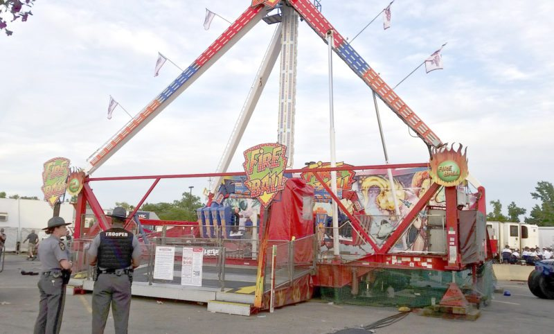 Authorities stand near the Fire Ball amusement ride after the ride malfunctioned injuring several at the Ohio State Fair, Wednesday, July 26, 2017, in Columbus, Ohio. Some of the victims were thrown from the ride when it malfunctioned Wednesday night, said Columbus Battalion Chief Steve Martin. (Jim Woods/The Columbus Dispatch via AP)