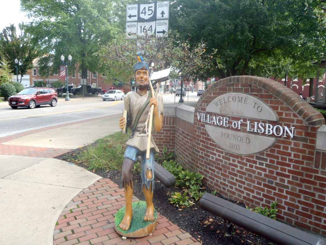 Morning Journal/Tom Giambroni A wooden statue of Johnny Appleseed stands like a sentinel in the Lisbon town square to welcome visitors as the village prepares for this weekend's Johnny Appleseed Festival, which runs Saturday and Sunday. The statue was made several years ago by local chainsaw artist Fred Gromley.