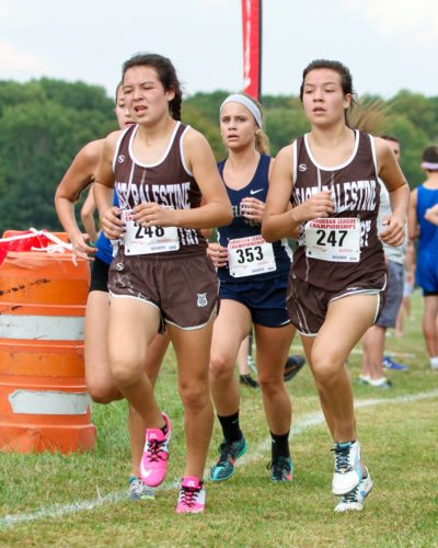 East Palestine's Hope Figley (left) and Faith Figley race at the Canfield Fairgrounds during the Suburburban League Championship Tuesday. (Morning Journal/Wayne Maris)