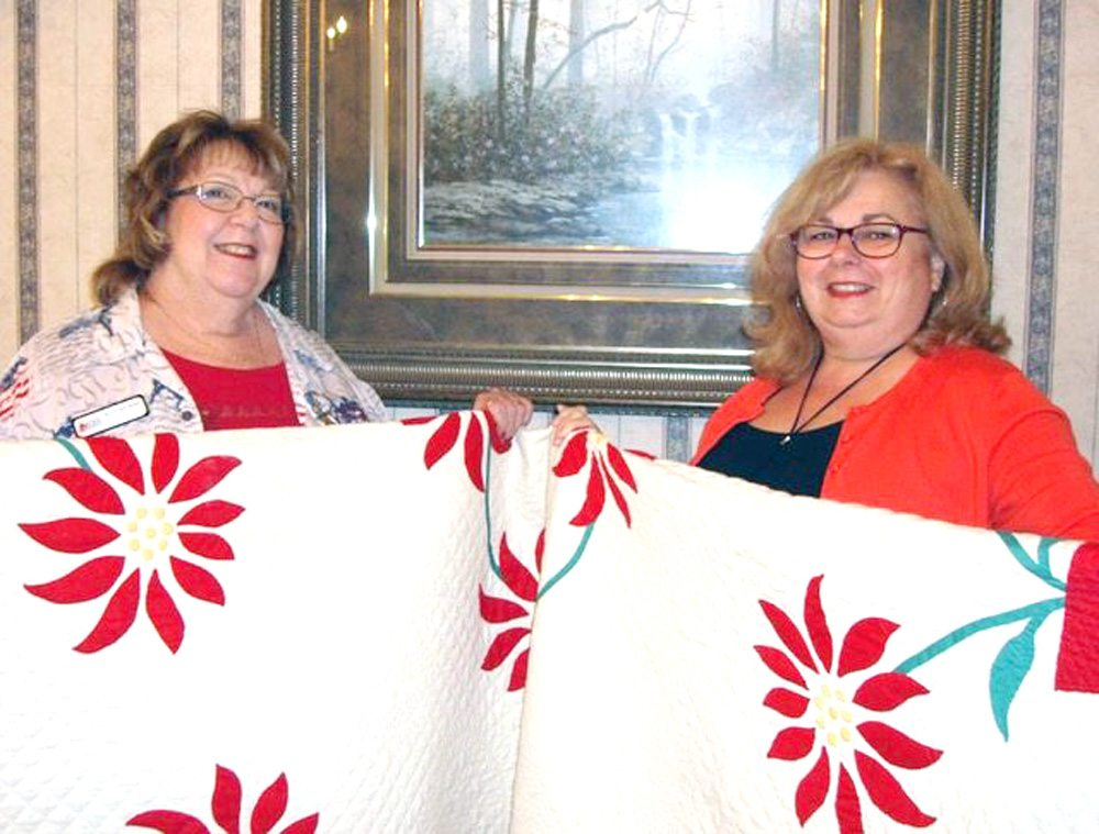 Submitted photo Deborah Himes (left) presents Rolayne Kasmer, Berlin Center, with the quilt that she won during the Historical Society of Columbiana Fairfield Townships quilt raffle at the Columbiana Street Fair. The applique poinsettia pattern quilt was made by Mildred Rowan and donated by Susan Rowan.