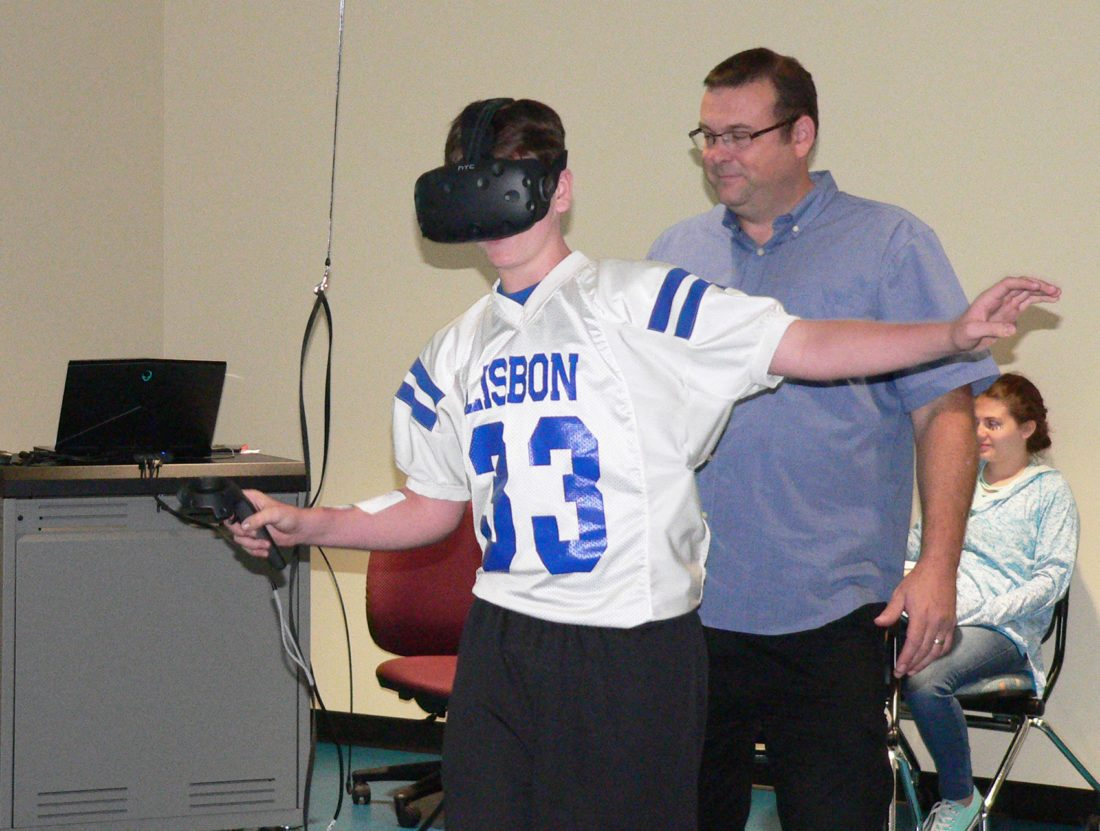 Morning Journal/Mary Ann Greier Lisbon freshman Gabe Damron tries to keep his balance while experiencing a virtual reality simulation of walking on a beam atop the Sears Tower in Chicago in the Virtual Reality Lab at the Kent State University Salem campus. Also pictured is Clayton Gellatly, the IT manager at Kent State.