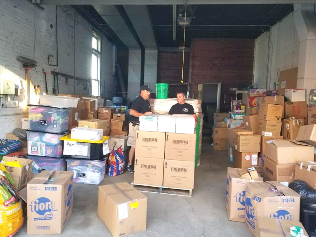 Submitted photo Mike Smith and Josh Kupka stand among hurricane relief supplies.