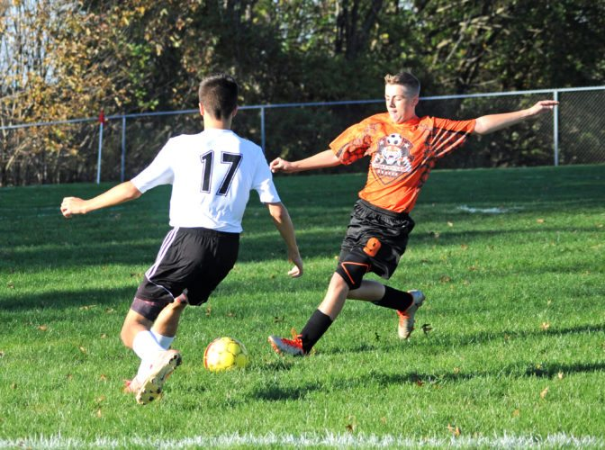 Wellsville's Charles Heffner kicks the ball past Crestview's Cory Dewell during Tuesday's sectional match.