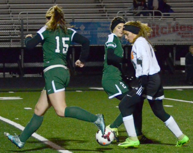Springfield's Kylee Kosek splits Elyria Catholic's Abby Birsic (left) and Riley Doll in regional semifinal action Tuesday night.