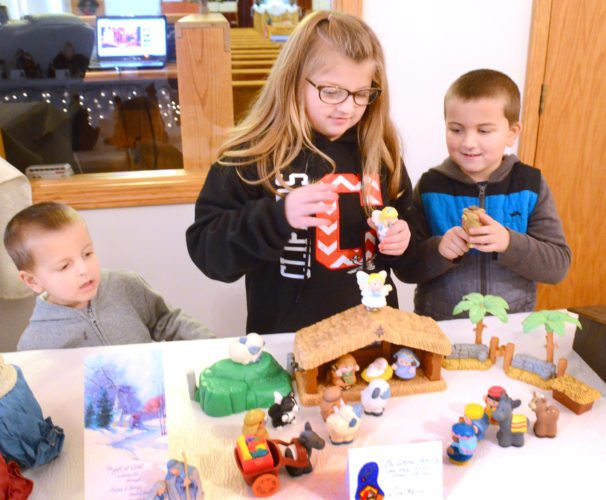Morning Journal/Patti Schaeffer Three-year-old Brodyn Aikens and his siblings, 8-year-old Jocelyn and 5-year-old Graydn of Columbiana put the finishing touches on their children's Nativity. The children are members of Zion Hill Church.