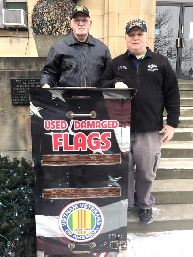 Morning Journal/Jo Ann Bobby-Gilbert Vietnam Veterans of America Chapter 1064, represented by (left) Ray Talbott and Bill Ash, has relocated a flag box for discarded American flags outside East Liverpool City Hall. Other such boxes are located around the area.