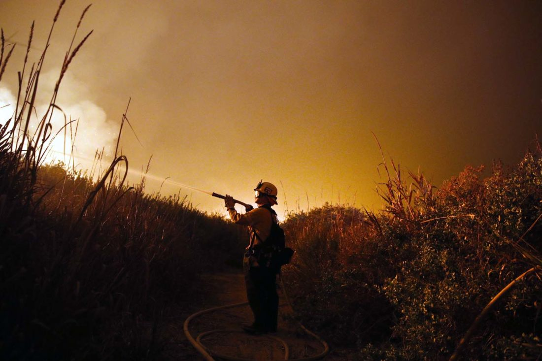 AP Photo/Jae C. Hong In this Dec. 7, 2017, file photo, firefighter Ryan Spencer battles a wildfire as it burns along a hillside toward homes in La Conchita, Calif.