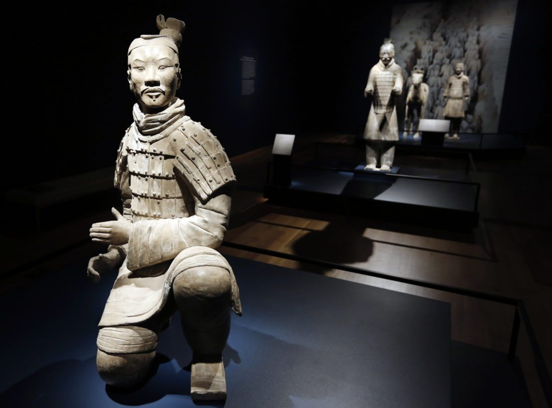 In a Tuesday, Dec. 12, 2017 photo, visitors look over some of the Terracotta Army soldiers on exhibit at the Virginia Museum of Fine Arts in Richmond, Va. The Museum has 10 of the majestic terracotta figures on display as part of an exhibit that tells the story of the first emperor of China and the time period he reigned. (AP Photo/Steve Helber)