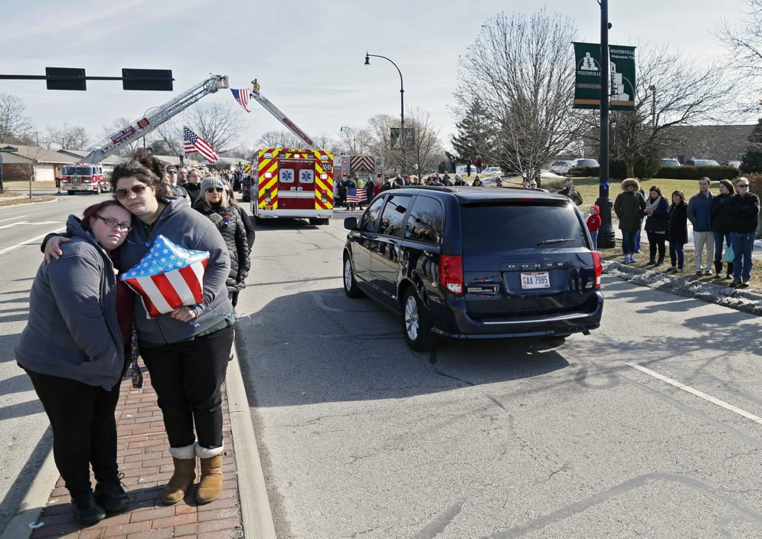 Kyle Robertson/The Columbus Dispatch via AP Lindsay Evans, right, holds friend Rachel Kaczmarek, left, as the the bodies of Westerville police officers Morelli and Joering pass by from the Franklin County coroner's office Monday. Evans and Kaczmarek had officer Morelli as a resource officer in middle school.