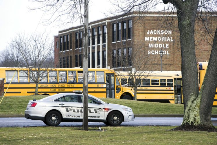 Bob Rossiter/The Canton Repository via AP A police car is parked outside Jackson Township Middle School in Massillon after a student shot himself after bringing a gun to school.