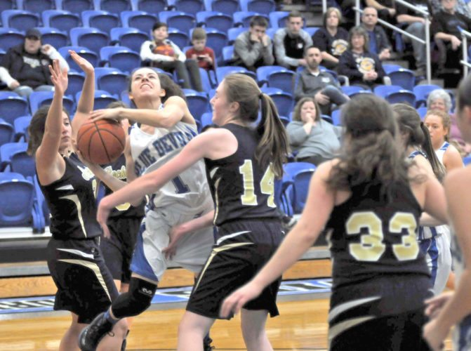 Lisbon's Izzy Perez goes up for a shot between Lowellville's Marah Bellis (left)and Madison Kelly during Wednesday's game. (Morning Journal/Chris Rambo)