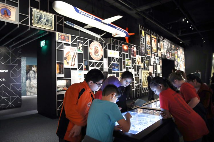 """A school groups explores an interactive touch table to learn about the objects and images on display at the """"Americans"""" exhibit at the Smithsonian's National Museum of the American Indian, Friday, Feb. 9, 2018, in Washington. The exhibit uses Native imagery to show how it permeates American culture. (AP Photo/Jacquelyn Martin)"""