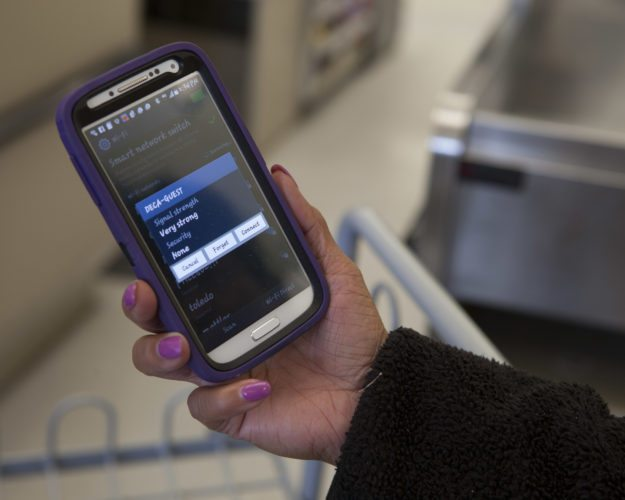 An F.E. Warren Commissary employee observes the Wi-Fi prompt on her smart phone on F.E. Warren Air Force Base, Wyo., April 23, 2015. The commissary activated its in-store Wi-Fi through Defense Commissary Agency's Commissary Patron Internet Mobile System. (U.S. Air Force photo by Lan Kim)