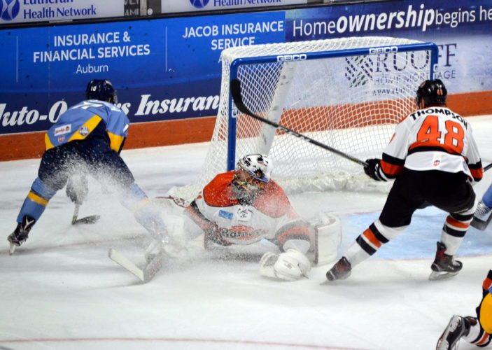 Komets goaltender Michael Houser forces Toledo's Shane Berschbach's scoring attempt away from the goal during the third period Saturday night. (By Blake Sebring of The News-Sentinel)