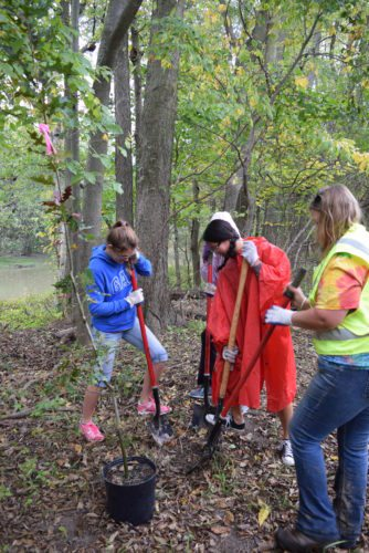 Save Maumee founder Abigail Frost-King gets a trio of Homestead High School Key Club members ready to dig into the earth with shovels to plant native trees Sunday morning in  Deetz Nature Preserve. (Photo by Lisa M. Esquivel Long of The News-sentinel)