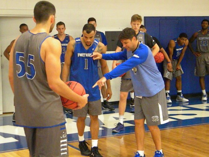 Fort Wayne men's basketball coach Jon Coffman instructs fifth-year senior guard Bryson Scott on positioning during a drill in a recent practice at the Gates Sports Center. (By Tom Davis of News-Sentinel.com)
