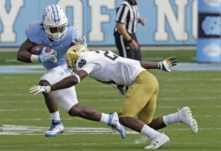 North Carolina's Michael Carter (8) runs while Notre Dame's Shaun Crawford looks to tackle him during the first half of a recent game in Chapel Hill, N.C (By The Associated Press)