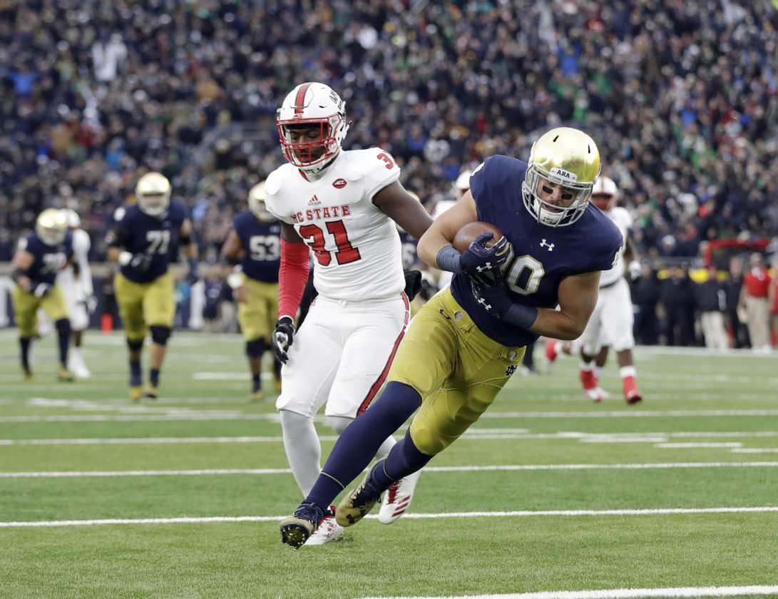 Notre Dame's Durham Smythe (80) makes a 25-yard touchdown reception against North Carolina State's Jarius Morehead (31) during the first half of a game Saturday  in South Bend. (By The Associated Press)