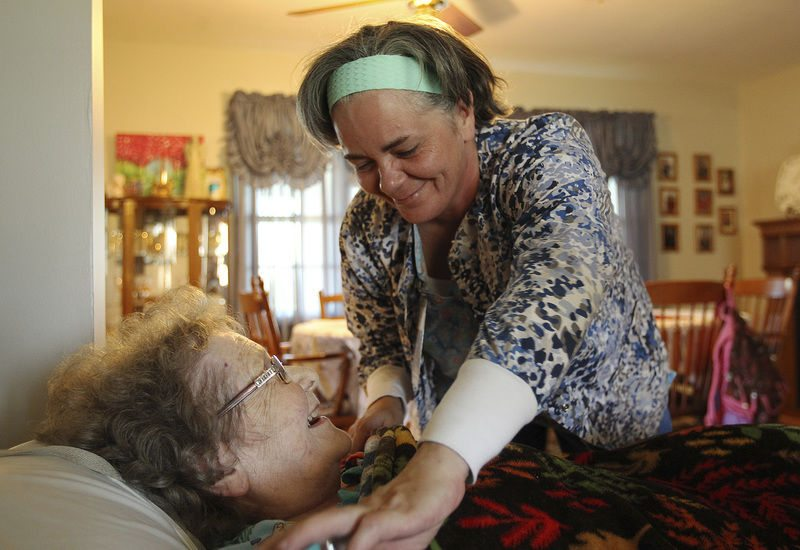 ORLEANS — Caregiver Shauntina Hickey drapes a blanket over client Lou Ann Crockett at Crockett's home near Orleans. Hickey, who was homeless before she landed a job as a personal-care attendant three years ago, was lauded with the Cheryl Atwood Award from the Indiana Association of Home and Hospice Care for her dedication to her clients. (Photo courtesy of the Times Mail)