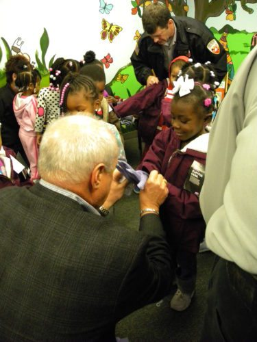 Steve Grashoff, left, president of Peerless Cleaners, helps a girl at MLK Montessori School try on new gloves during the kickoff Wednesday for the annual Coats for Kids winter clothing collection drive. Peerless is a drop-off location and cleans gently used coats before they are distributed to children in need through area schools and social-service agencies. (By Kevin Kilbane of News-Sentinel.com)
