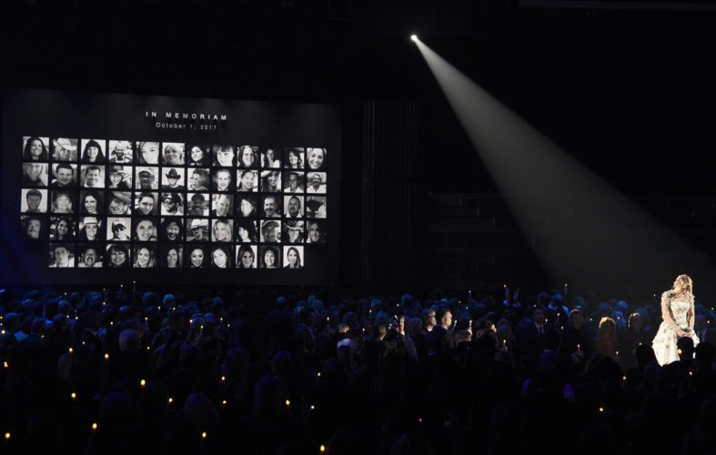 """Carrie Underwood pauses during an emotional performance of """"Softly and Tenderly"""" during an In Memoriam tribute at the 51st annual CMA Awards at the Bridgestone Arena on Wednesday, Nov. 8, 2017, in Nashville, Tenn. Pictured on screen are victims of the Route 91 Harvest mass shooting. (Photo by Chris Pizzello/Invision/AP)"""