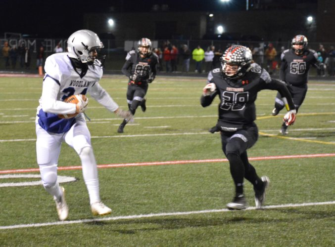 Woodlan receiver Aaron Hahn attempts to escape from Eastbrook's Edward Keasling during Friday's semistate game in Marion. (By Justin Kenny of news-sentinel.com)