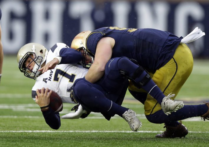 Navy quarterback Garret Lewis (7) is tackled by Notre Dame defensive lineman Jerry Tillery (99) during the first half of a game in South Bend Saturday. (By The Associated Press)