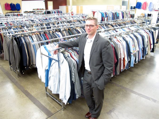 Blue Jacket Inc. Executive Director Tony Hudson stands in 2013 amid clothing the not-for-profit agency provides to clients seeking employment. The agency is partnering with University of Saint Francis to hold a pop-up shop during Holly Trolley on Saturday. (News-Sentinel.com file photo)