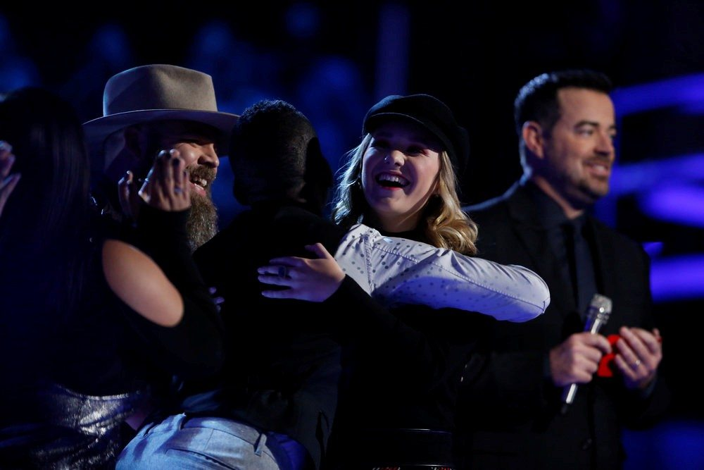 "Addison Agen, right, gets a congratulatory hug from fellow Team Adam member Jon Mero after host Carson Daly announced Addison was saved by viewer overnight voting following Monday night's live show on ""The Voice."" (Courtesy of NBC)"