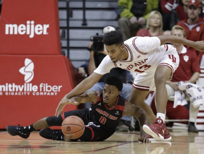 Arkansas State's Ty Cockfield and Indiana's Juwan Morgan reach for a loose ball during the second half of a game Wednesday in Bloomington. (By The Associated Press)