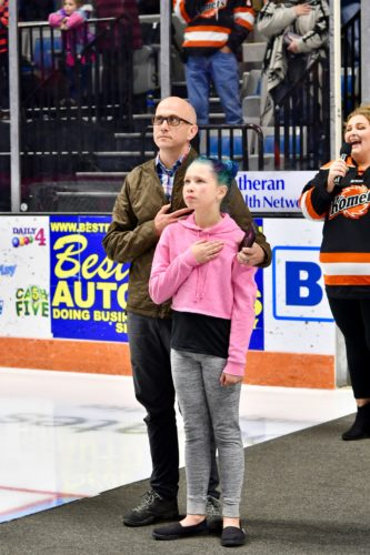 Army Sergeant First Class Brian Hunt and his daughter Bailey stand during the national anthem before Thursday's Komets game. (Photo courtesy of Jeremy Faux, Eye to Eye Photos)