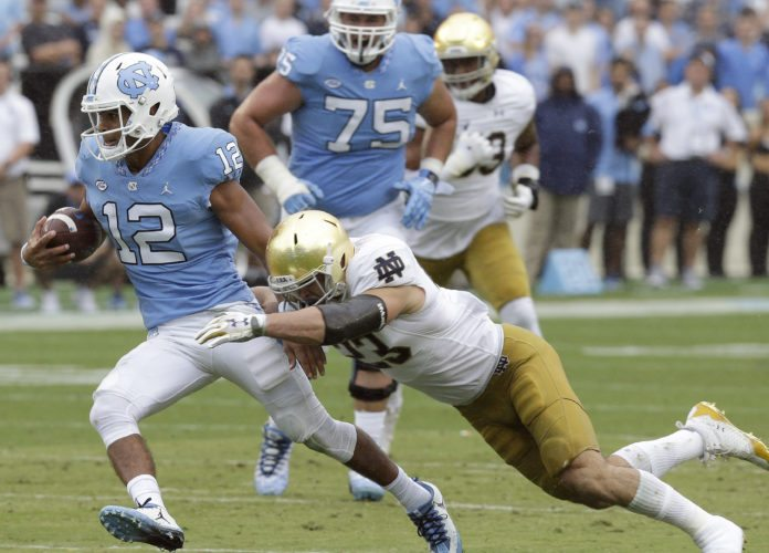 Notre Dame's Drue Tranquill reaches to tackle North Carolina quarterback Chazz Surratt (12) during the first half of a game this past season in Chapel Hill, N.C. (By The Associated Press)