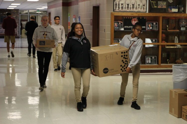 Concordia Lutheran High School students sophomore Briana Whitt, left, and freshman Aubrie Williams carry a box of Christmas gifts for Allen County Christmas Bureau families to the school's front entry area Tuesday morning. The gifts then were loaded on a truck for delivery to the Christmas Bureau. Behind them, carrying a box, is  junior Natalie Shutt. (Courtesy of Concordia Lutheran High School)