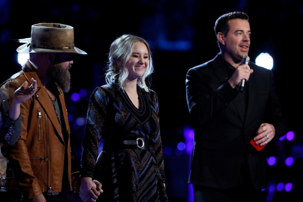 "Fort Wayne's Addison Agen, center, reacts on Tuesday night's live results show for ""The Voice"" after host Carson Daly, right, announces viewer votes have made her one of the Top 8 performers competing on next week's show. At left is Addison's teammate Adam Cunningham, who also advanced to next week's show.  (Photo by Trae Patton/NBC)"