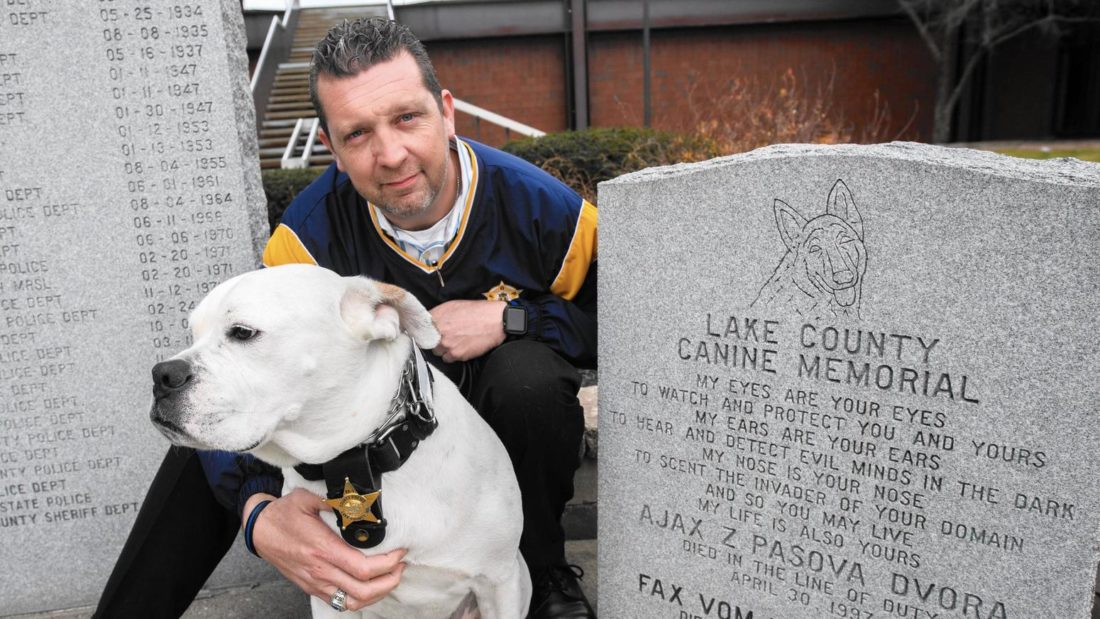 Officer Joe Hamer poses for a photo with his police dog, Bruno, near the Lake County Canine Memorial at the Lake County Sheriff's Department in Crown Point on Monday, Dec. 4, 2017. (Photo courtesy of the Post Tribune through the Associated Press)