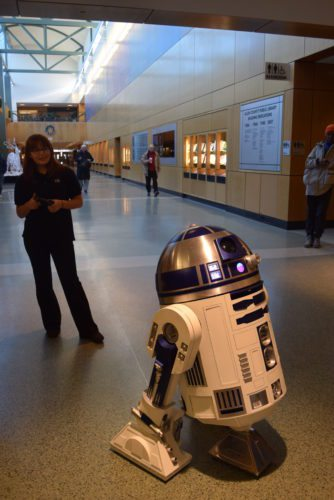 """Alex Forsythe, 18, operates the R2-D2 she built and uses a PlayStation 2 controller to operate it Sunday afternoon at Allen County Public Library's """"Star Wars Fest."""" (Photo by Lisa M. Esquivel Long of News-Sentinel.com)"""