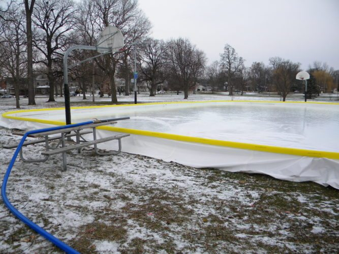 Fort Wayne Parks and Recreation Department workers installed the liner Monday morning in the temporary ice rink at Lakeside Park and began filling it with water. (By Kevin Kilbane of News-Sentinel.com)