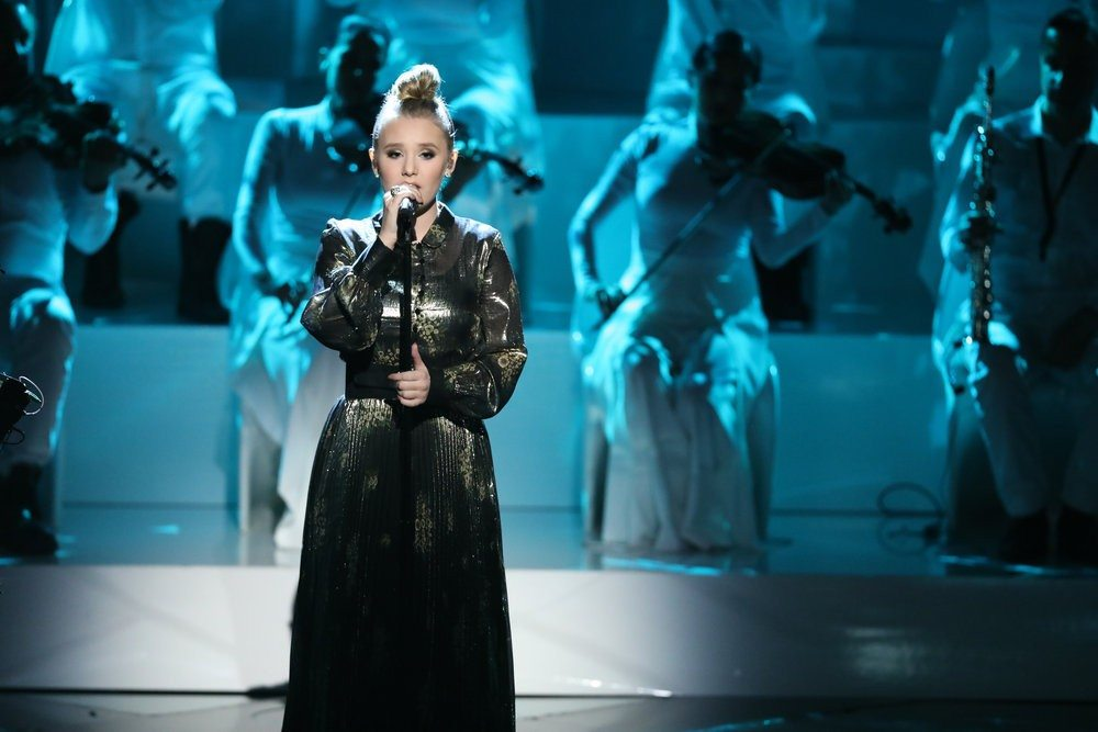 """Backed by an orchestra, Addison Agen, 16, of Fort Wayne sings Joni Mitchell's """"Both Sides Now"""" during her solo performance Monday night on """"The Voice."""" The performance ranked No. 2 ont he iTunes Top 200 Songs chart as of noon today, which will give her bonus votes going into tonight's results show at 8 p.m. on NBC.  (Photo by Tyler Golden/NBC)"""
