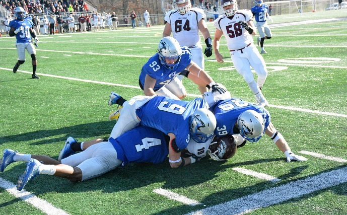 Saint Francis defensive players Lee Stewart (4), Piercen Harnish (9) and Eric Dunten (39) pile on a Morningside back during the Cougars' semifinal win on Dec. 2 at Bishop D'Arcy Stadium. (Photo by Reggie Hayes of news-sentinel.com)