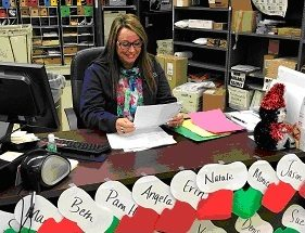 Acting Postmaster Beth Jungels reads some of the letters that children have sent  to the Syracuse Post Office. The names in front of her are those of the USPS employees and citizens who have volunteered for Operation Santa. (Photo courtesy of U.S. Postal Service)