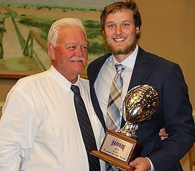 Saint Francis quarterback Nick Ferrer, right, holds the NAIA Player of the Year award as he poses with coach Kevin Donley on Friday in Daytona Beach, Fla., (Photo courtesy Bill Scott/University of Saint Francis)