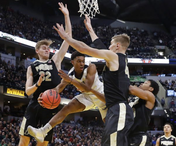 Butler's Aaron Thompson makes a pass against Purdue's Matt Haarms (32) and Isaac Haas (44) during the first half of a game Saturday in Indianapolis. (By The Associated Press)