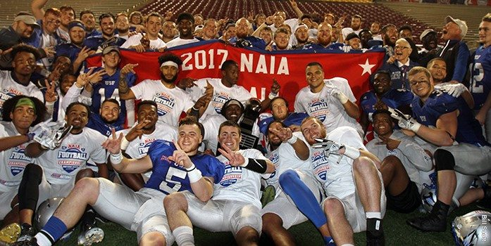 Saint Francis players pose with the 2017 NAIA national championship banner after a 24-13 win over Reinhardt on Saturday in Daytona Beach, Fla. (Photo courtesy Bill Scott/University of Saint Francis)