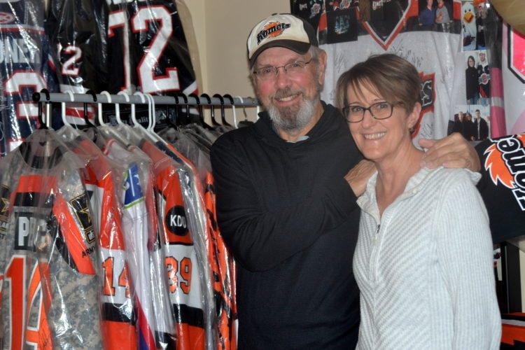 Bill Oberg and Sue Hansen post with some of the 42 Komets jerseys they have collected over the last 10 years. (By Blake Sebring of News-Sentinel.com)